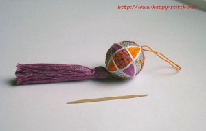 Violet and orange interwoven spindle temari